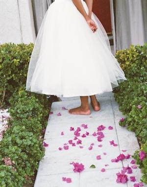Femme portant une robe de mariée, quelques pétales sont sur le sol.